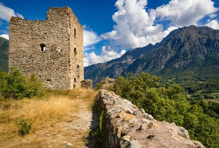 Ruins of Saint-Firmin castle (14th century medieval construction also known as Le Fort) at the entrance of Valgaudemar valley in Hautes-Alpes with view on the Petit Chaillol mountain peak (Le Blanc du Peyron). Summer in the Southern French Alps. France