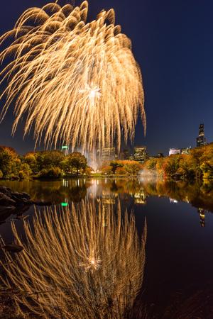 Central Park Fireworks celebrating the Marathon reflecting on the Lake. Midtown Manhattan, New York City Stock Photo