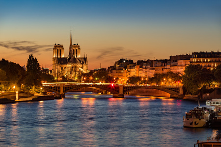 sully: Notre Dame de Paris Cathedral, Seine River and the Ile Saint Louis at twilight. Summer evening with the Sully Bridge and city lights in the 4th Arrondissement of Paris. France Stock Photo