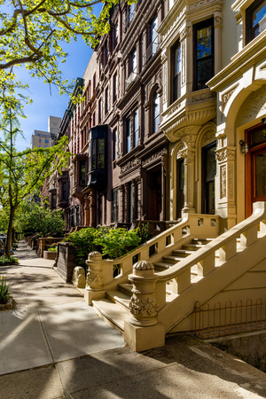 townhouses: Row of brownstones with doorsteps and ornament in morning light. Upper West Side Street, Manhattan, New York City