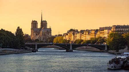 Notre Dame de Paris Cathedral, Ile Saint Louis, the Sully Bridge, and the Seine River at sunset in Summer. 4th Arrondissement of Paris. France