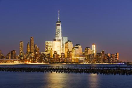 Lower Manhattan skycrapers illuminated at twilight with the Hudson River. Manhattan, New York City