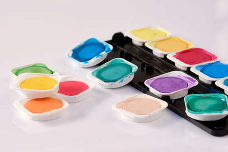 The bright variegated colours of a used watercolor box lying isolated on white background.