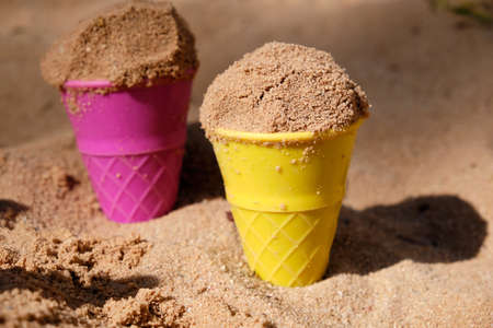 Closeup of two colorful sand moulds in shape of ice cream cones with sand in it are sticking in the sand of a sand pit on a sunny day with shadows 版權商用圖片