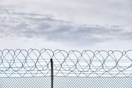 Close-up of a high chain-link fence with razor-barbed wire at the top protecting an airport in Germany Stock Photo