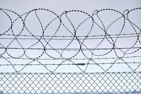 Close-up of a high chain-link fence with razor-barbed wire at the top protecting an airport in Germany