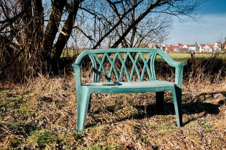Rural February landscape with meadows and trees in Germany with an empty weathered plastic bench inviting pedestrians zu linger in the sun Stock Photo