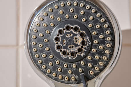 Close-up of an old used silver and grey colored shower head with limescales in the bathroom in front of white tiles