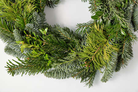 Closeup of a bare fresh and green Advent wreath without christmas decoration lying isolated on a white glass plate