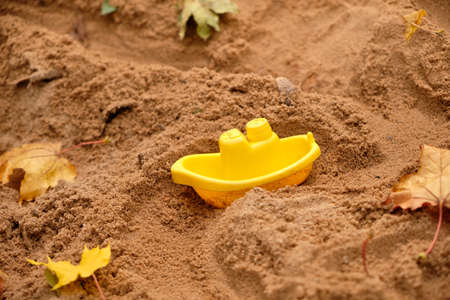Small yellow plastic toy boat is dirving through the sand with autumn leaves in the sand pit on a playground