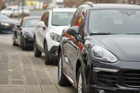 Nuremberg, Germany - December 02, 2019: Headlight of a big black Porsche SUV car parking in a row together with other cars on the pavement in the city. Éditoriale