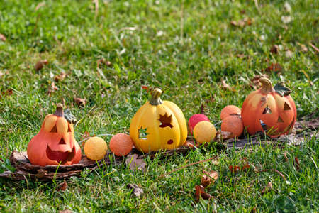 Smiling orange  and yellow Halloween decoration lying in the grass i the garden. Seen in Germany, Bavaria, in October. Banco de Imagens