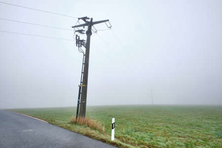 Countryside road with  power pole in no man's land in a foggy autumnal countryside landscape with no sight. Seen in Germany near Oedenberg, Bavaria in October.