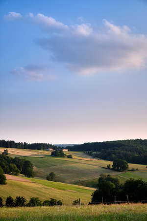 Beautiful evening landscape in the Spessart area in Germany with clouds in the blue sky and agricultural fields