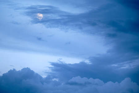 The moon hiding behind some clouds on an dramatic evening sky in summer in Germany