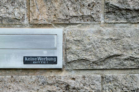 Nuremberg, Germany - May 16, 2019: Silver mailbox in a ray wall made of stones with a sign that says