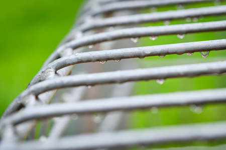Raindrops hanging on a gray grid of a iron soccer goal on a playground with a green meadow in the background