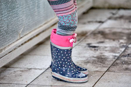 The pair of colourful rubber boots of a girl child playing, standing and jumping around in a rain puddle on some muddy white tiles of a balcony