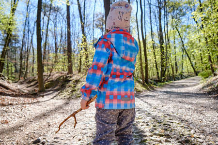 Rear view of 4 year old child girl holding wooden stick in hand and thinking about which way to choose in a beautiful bright springtime forest on a sunny day. Seen in Germany in April. 版權商用圖片