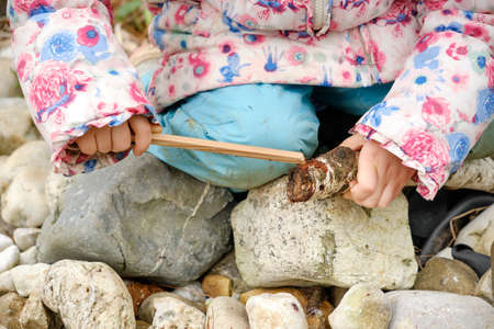 Closeup of low section of 4 year old  caucasian child girl in warm clothing sitting on stones in the garden and playing with two wooden sticks. Seen in March in Germany.
