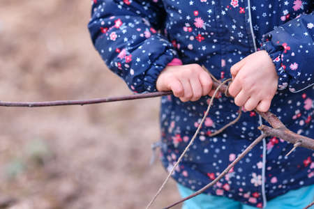 Closeup of midsection of a caucasian child girl in warm winter clothing playing with a wooden twig and a string and trying to make a knot. Seen in Germany in January