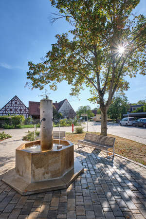 Haimendorf, Germany - September 16, 2019: A beautiful autumn day in the Franconian village Haimendorf near Röthenbach an der Pegnitz with a fountain in front of a beautiful tree an benches on a sunny day