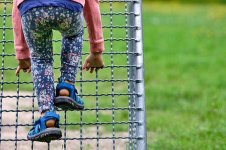 Rear view of the lower section of a child in sandals and casual clothing climbing up the metal grid of a goal on a playground