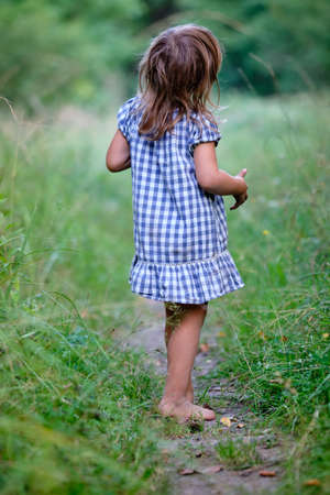 Rear view of a young child girl with unshod feet in  summer dress is standing on a narrow path in a high meadow