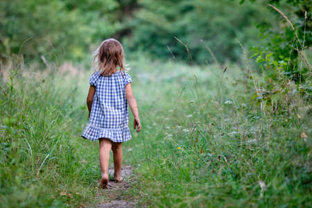 Rear view of a young child girl with unshod feet in  summer dress is walking on a narrow path in a high meadow