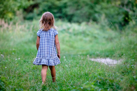 Rear view of a young child girl with unshod feet in  summer dress is walking on a natural meadow in nature