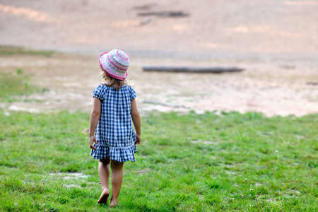 Rear view of a young child girl with unshod feet in summer dress walking on a natural meadow in nature Banque d'images