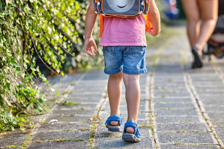 Rear view of a 3-4 year old child walking behind his mother with a rucksack on the sidewalk on a sunny summer day