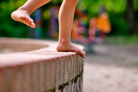 Low section of a caucasian child girl who is standing barefoot on a little stone wall with sandy feet in summer Banque d'images