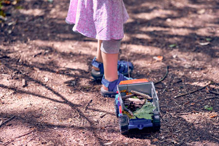 Lower part of a 3 year old girl pulling a toy truck with leaves, stones and wooden sticks in the forest