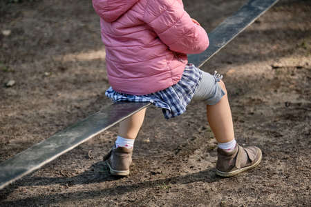 Low section of a child girl in casual clothing playing and jumping on a black slack line on a playground