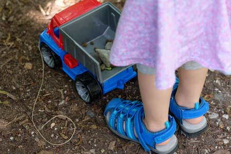 Lower body part of a young girl of about 3 years in summer clothing standing with her toy truck with some stones in it in the forest