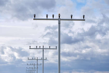 Part of an approach lighting system of an airport against overcast sky in March in Germany