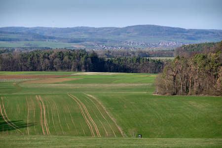 A beautiful view into the Franconian Switzerland from Tauchersreuth in direction of Eckenhaid and Pettensiedel in Germany with a sunny spring landscape with green meadows, fields and forest in March 2019