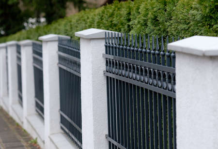 A beautiful elegant vintage gray and white fence made out of metal and stone with a green hedge in Germany in March 2019