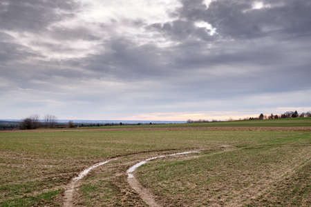 Agricultural field with tractor tracks after rain on a moody day in March in Germany