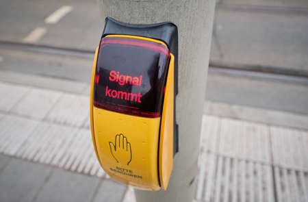 Close-up of button for pedestrians to touch at some traffic lights in Germany in order to get green light. It says