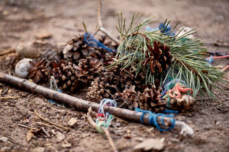A pile of pine cones on the ground with some needles, blue cords and twigs on the ground created by some children in the forest. Seen in Germany in April 2019