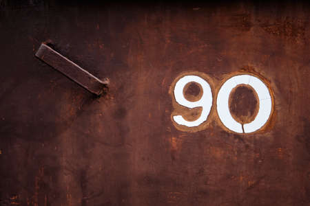 The dark brown and rusty door of an dustbin box with the number 90 of the reffering house on it. Seen in Germany, April 2019