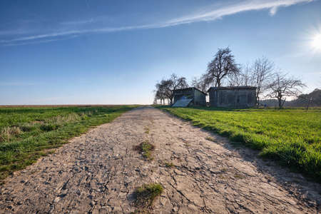 Old and decaying gravel road with some old huts and bare trees as well as green grass and meadows. Seen in Germany in March 2019