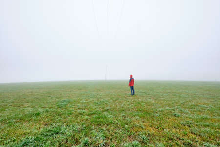 Rear view of man in red jacket standing on a green meadow and looking into a foggy nowhere landscape. Seen in October in Germany, Bavaria near Oedenberg.