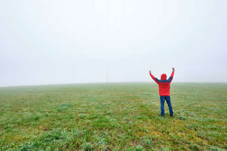 Rear view of man in red jacket standing on a green meadow and raising his arms in joy in front of a foggy nowhere landscape. Seen in October in Germany, Bavaria near Oedenberg.