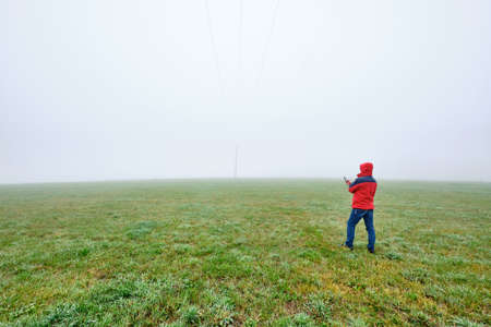 Rear view of man in red jacket standing on a green meadow and looking on his smartphone in front of a foggy nowhere landscape. Seen in October in Germany, Bavaria near Oedenberg.