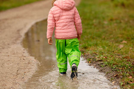 Rear view of a child girl in green waterproof pants and rubber boots walking through a huge rain puddle alongside a gravel road in the forest on a rainy autumn day in October in Germany Banque d'images