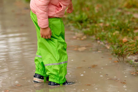 Low section of a child girl in green waterproof pants and rubber boots standing in a huge rain puddle in the forest on a rainy autumn day in October in Germany Banque d'images