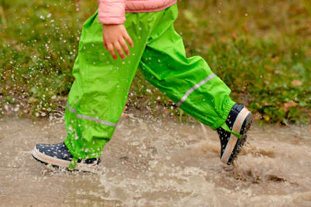 Side view of low section of a child girl in green waterproof pants and rubber boots running through a huge rain puddle in the forest on a rainy autumn day in October in Germany Banque d'images